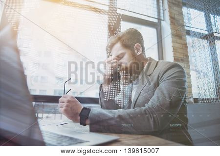 Feeling disappointed. Cheerless bearded man sitting at the table and holding glasses while feeling gloomy
