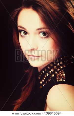 Young people teenage concept - pensive serious woman portrait fashion teenager girl wearing blouse with gold metal stud on black