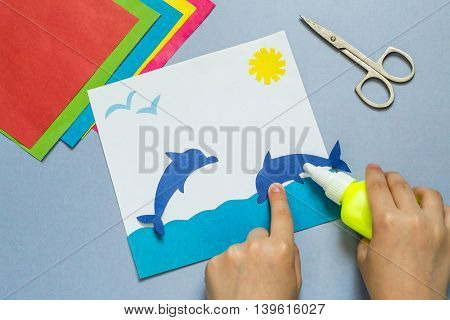 Child glues a dolphin out of paper making the applique on the marine theme. The idea for children's creativity an art project made of paper. Sheets of colored paper glue scissors