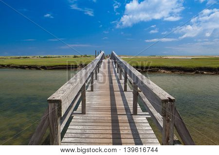 Walkway to the dunes wooden walkway extends over marshland toward the distant dunes and ocean In Sandwich Cape Cod Massachusetts USA