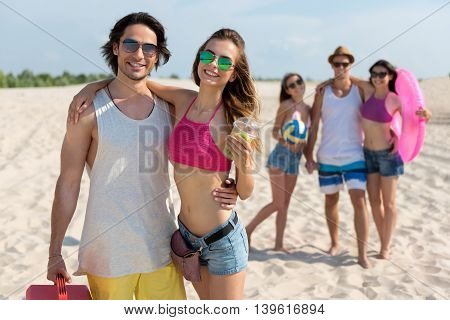 On the edge of delight. Cheerful smiling couple embracing and standing on the beach while their friends having fun in the background