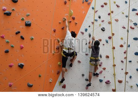 Two asian women climbing indoor vertical wall