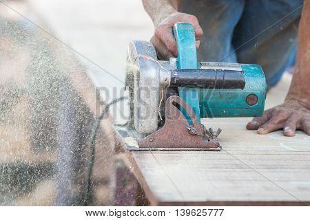 Man Using A Circular Saw To Cut The Wood