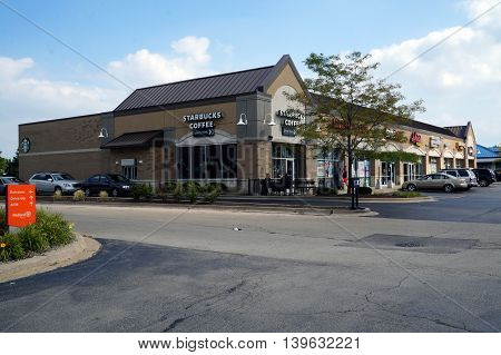 JOLIET, ILLINOIS / UNITED STATES - AUGUST 30, 2015: A Joliet strip mall includes a Starbucks Coffee Shop with a drive-thru service, plus several other businesses.