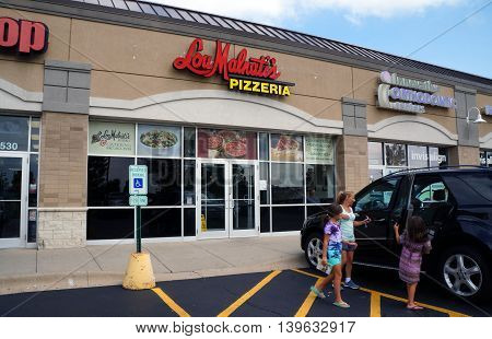 JOLIET, ILLINOIS / UNITED STATES - AUGUST 30, 2015: One may eat pizza at Lou Malnati's Pizzeria, in a Joliet strip mall.