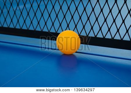yellow ball hits the bottom of the net on a blue pingpong table close up