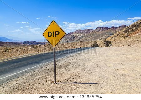 Scenic Road Artists Drive In Death Valley With Colorful Stones, Hills With Minerals,  Road Sign Dip