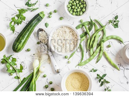 Raw ingredients - rice cous cous zucchini green beans and peas olive oil on a light background. Healthy vegetarian food