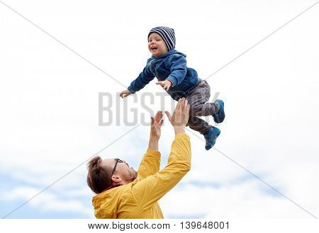family, childhood, fatherhood, leisure and people concept - happy father and little son playing and having fun outdoors