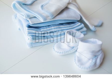 clothing, babyhood, motherhood and object concept - close up of baby bootees and pile of clothes for newborn boy