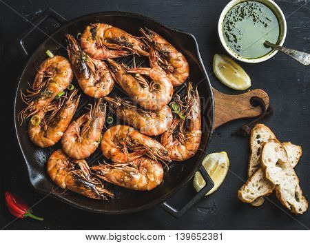 Roasted tiger prawns in iron grilling pan with fresh leek lemon bread and pesto sauce over black background top view