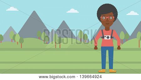 An african-american woman with a digital camera on her chest. Tourist with a digital camera standing on the background of mountains. Vector flat design illustration. Horizontal layout.