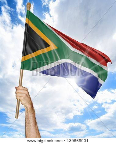 Person's hand holding the South African national flag and waving it in the sky, 3D rendering