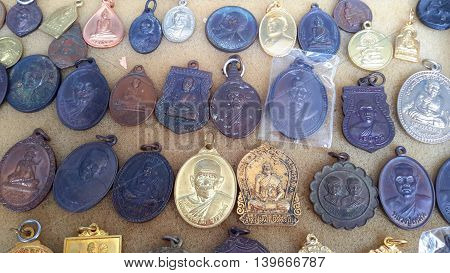 Thai bronze good luck monk amulets for sale at the Songkhla market, Thailand