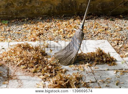 Pile of leaves with a broom being swept up
