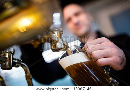 Brewer filling beer in beer glass from beer pump in bar