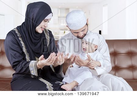Portrait of two middle eastern parents teaching their son to pray while sitting on the sofa at home