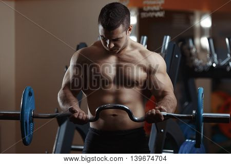 Fitness man exercising with barbell in gym. Fitness man deadlift barbell in the gym. Fitness man in the gym. Sports and fitness - concept of healthy lifestyle.