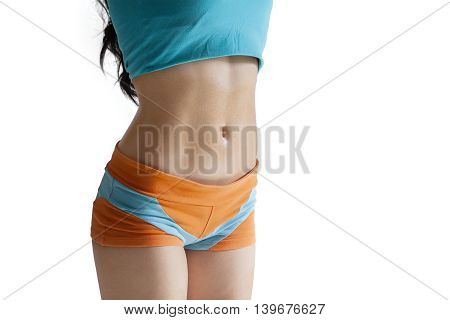 Close up of stomach of healthy woman wearing sportswear in the studio isolated on white background