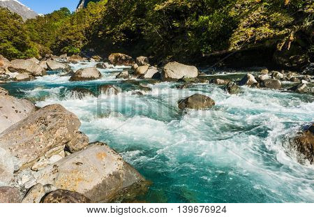 Beautiful turquoise creek with snowy peaks near the Milford highway. Fiordland National Park, New Zealand