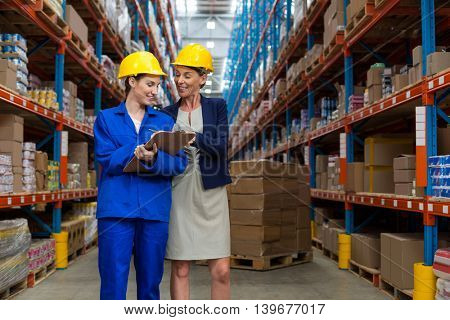 Coworkers looking at clipboard in warehouse