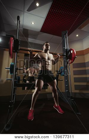 Bodybuilder squatting with a barbell. Bodybuilder working with barbell. Fitness man doing squats with the barbell at the gym. Smith Machine in the gym. Fitness man in the gym. Perfect healthy figure