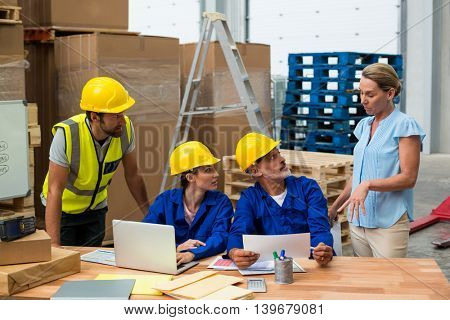 Warehouse worker listening to their manager in warehouse
