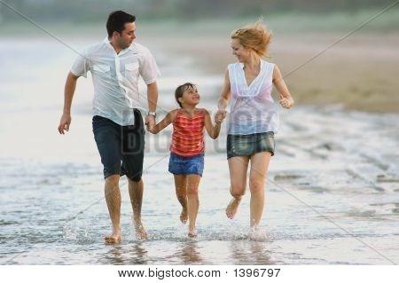 Family Excercising At The Beach
