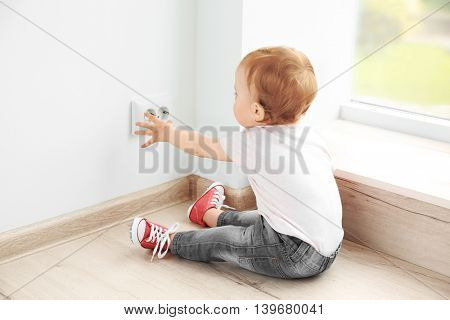 Baby playing with electrical outlet on floor at home