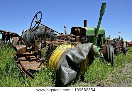 An old tractor without a tire and inner tube laying on the rim.