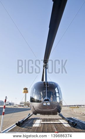Helicopter at the airport, in front of blue sky.