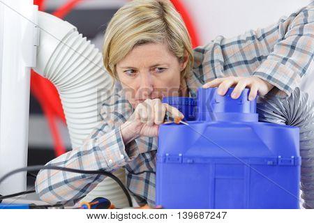female electrician reapiring machinery