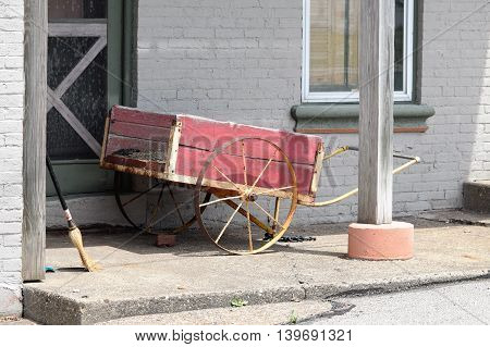 a old two wheeled hand cart sits forgotten.