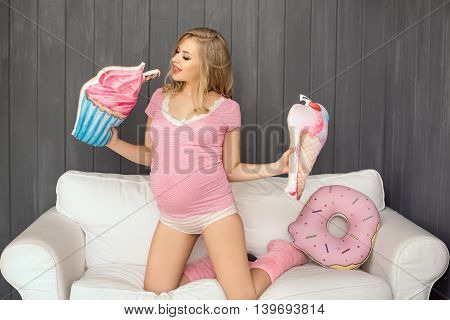 Beautiful pregnant woman looking food and sitting on a couch. The happiest time for every woman. Ice cream and doughnut in the hands of a pregnant girl