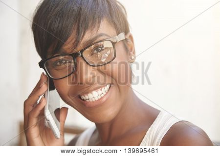 Close Up Portrait Of Happy Dark-skinned Woman With Short Pixie Haircut Wearing Glasses, Having Phone
