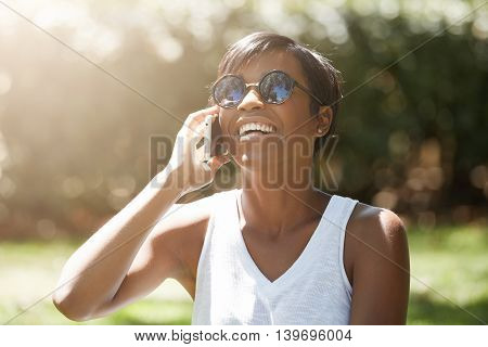 Half Profile Of Beautiful Young Woman Wearing Casual White Top And Stylish Shades Laughing While Tal