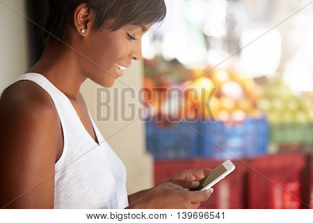 Profile Of Smiling Young Dark Skinned Woman Leaning Against The Wall, Using Wireless Internet Connec