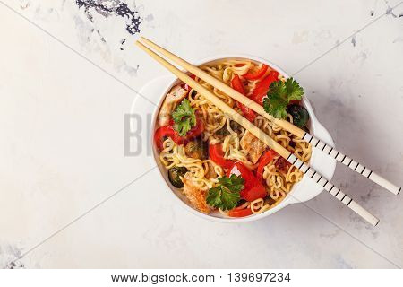 Asian noodles with vegetables and chicken top view.
