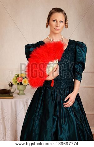portrait victorian woman with red feather fan with table in background
