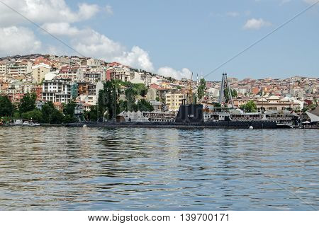 ISTANBUL TURKEY - JUNE 5 2016: View looking north across the Golden Horn towards the Rami M Koc Museum of transport on a sunny afternoon in Istanbul. There's a World War II submarine together with other ships on display.