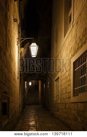 A dimly lit alley at night, could be from medieval times