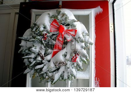 Christmas Blizzard Wreath on door covered with snow.