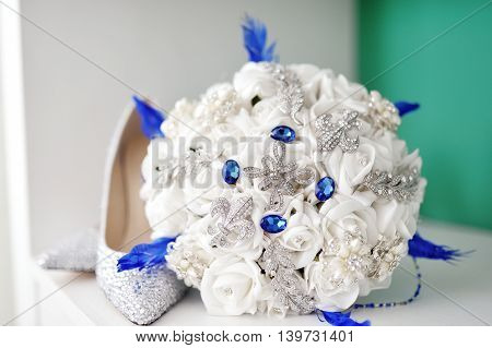 White artificial wedding bouquet and bride shoes
