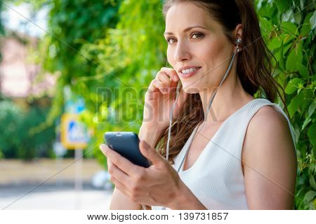 Portrait of beautiful woman brunette listening to music with headphones in park outdoors