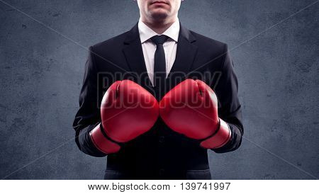 A well dressed sales person standing with red boxing gloves on his hand in front of urban grey wall background concept.