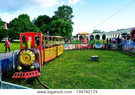 VELIKY NOVGOROD RUSSIA - JUNE 11 2016. Children's attraction - a small steam train on the playground equipped at Yaroslavs Courtyard in the City Day in Veliky Novgorod
