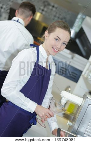 worker working with colleague at counter in ice cream parlor poster