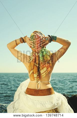 Young fashion woman back, girl sitting on a stone against seascape, dressed in african safari style with headband on a head, hands up enjoying the summer, boho chic