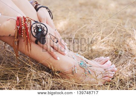 Handcrafted bracelets on a woman legs and hands, dreamcatcher jewelry, close up, white pedicure and manicure, boho chic style, sunny outdoor photo on a straw, focus on a hand