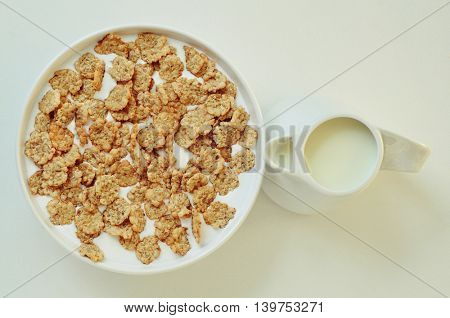 high-angle shot of a white bowl with breakfast cereals soaked in milk and a ceramic milk pot on a white table